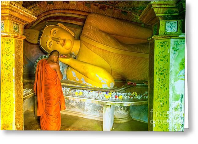 praying buddhist monk by a lying buddha in Sri Lanka Greeting Card by Gina Koch