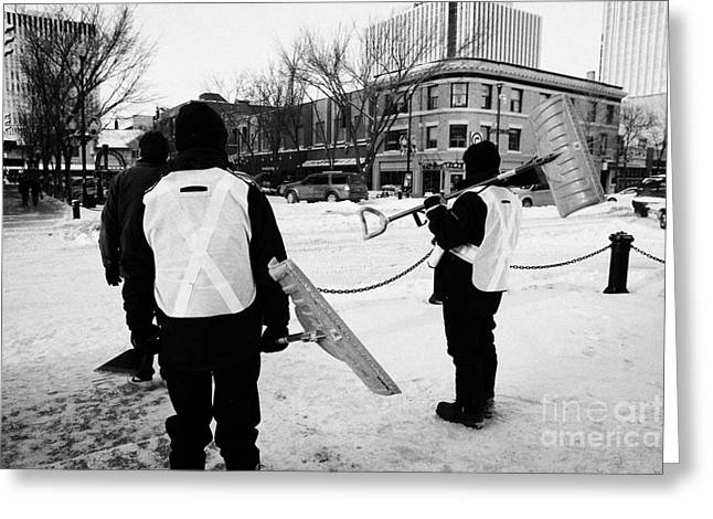 public workers clearing snow and ice off the sidewalks in downtown Saskatoon Saskatchewan Canada Greeting Card