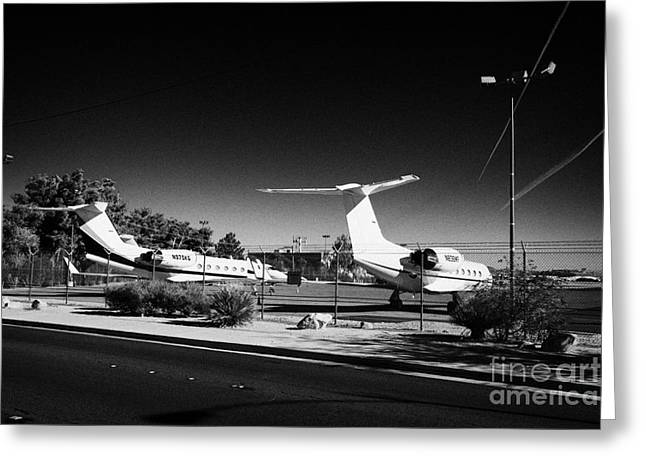 road passing security chain link fencing on the perimeter of mccarran airport Las Vegas Nevada USA Greeting Card by Joe Fox