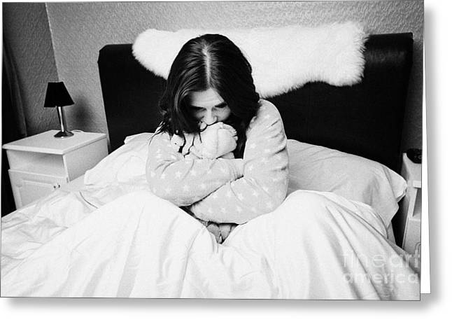 Sad Early Twenties Woman Holding Cuddly Dog Soft Toy In Bed In A Bedroom Greeting Card by Joe Fox