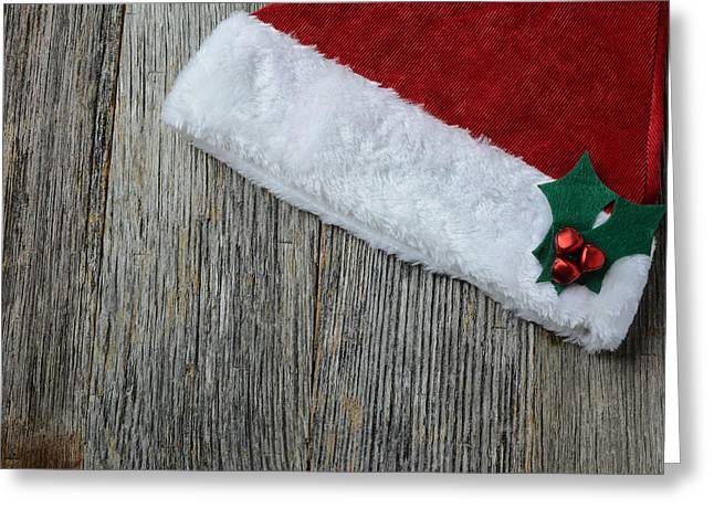 Santa Hat On Rustic Wood Background Greeting Card by Brandon Bourdages