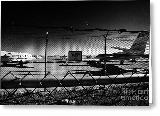 security chain link fencing with warning restricted area sign on the perimeter of mccarran airport L Greeting Card by Joe Fox