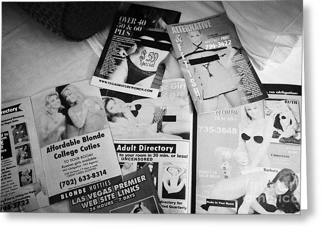 selection of leaflets advertising girls laid out on a hotel bed in Las Vegas Nevada USA Greeting Card by Joe Fox