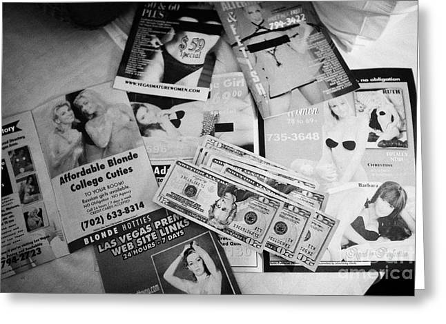 selection of leaflets advertising girls laid out on a hotel bed with us dollars cash in Las Vegas Ne Greeting Card by Joe Fox