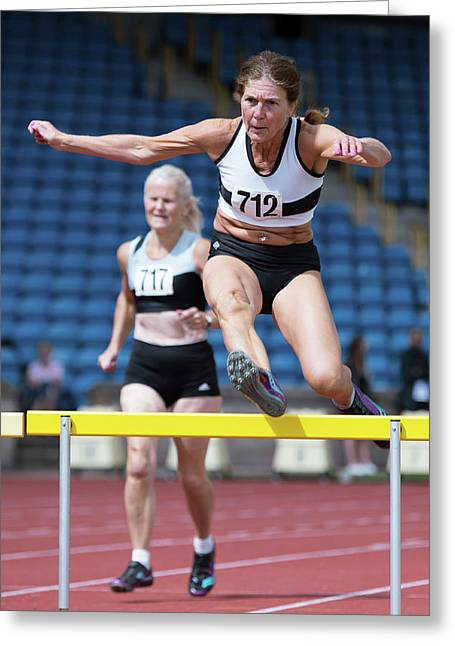 Senior Female Athlete Clears Hurdle Greeting Card by Alex Rotas