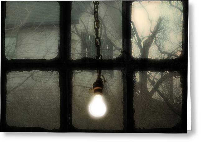 Lit Light Bulb Shines In Old Window Greeting Card by Gothicrow Images