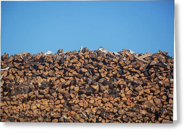 Stack Of Firewood Pile Against Blue Sky Greeting Card by Panoramic Images