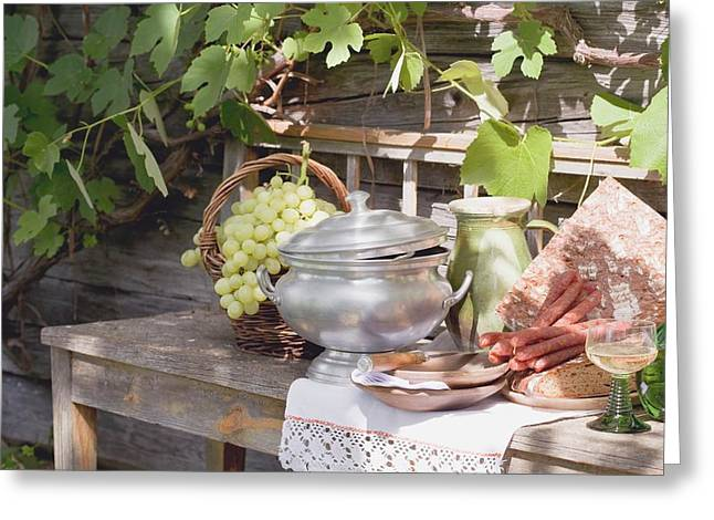 Still Life With Grapes, Bread, Sausages And Wine In Front Of Farmhouse Greeting Card