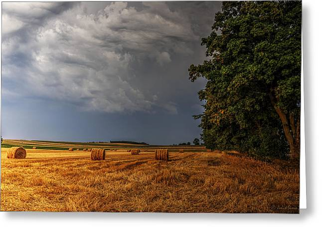 Storm Clouds Over Harvested Field In Poland Greeting Card