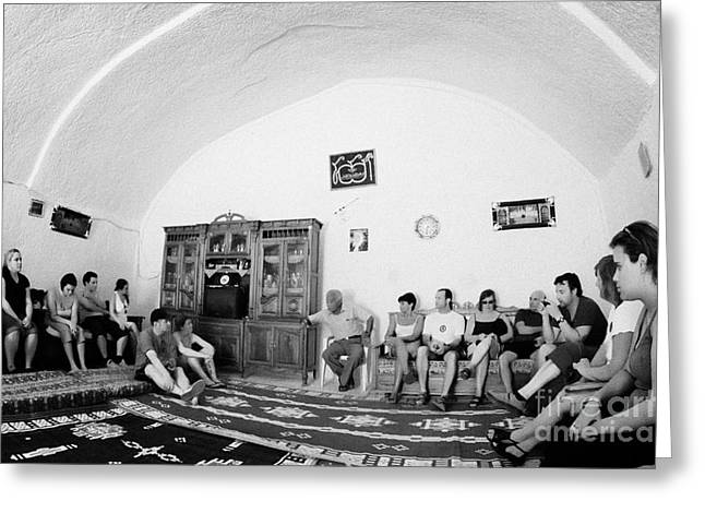 tour guide and coach load of british tourists the inside of main cave room of berber troglodyte underground dwelling at Matmata Tunisia Greeting Card