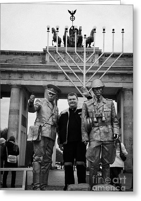 tourist posing for photograph with silver painted street entertainer dressed as east german guard Brandenburg gate Berlin Germany Greeting Card by Joe Fox