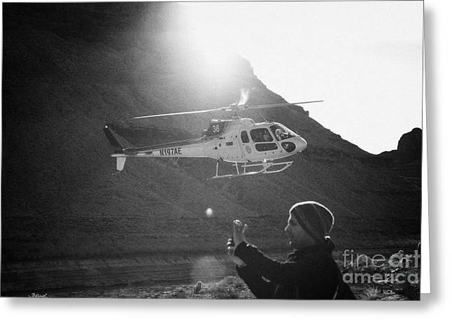 tourist taking photos with smart phone as papillon helicopter tours comes in to land in the Grand ca Greeting Card by Joe Fox