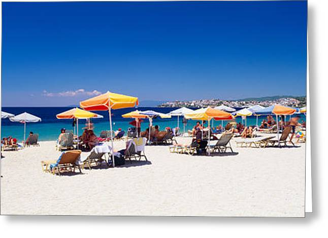 Tourists On The Beach, Porto Carras Greeting Card by Panoramic Images