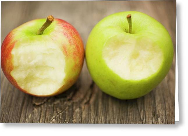 Two Apples With Bites Taken On Wooden Background Greeting Card