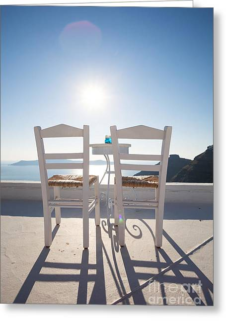 Two Empty Chairs Overlooking Blue Mediterranean Sea In Santorini Greeting Card by Matteo Colombo