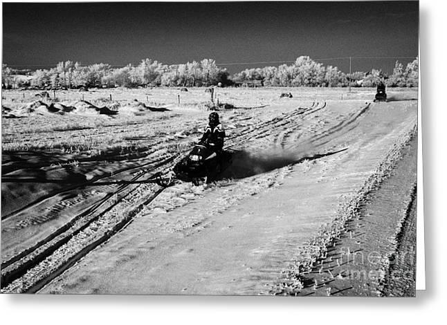 two men on snowmobiles crossing frozen fields in rural Forget Saskatchewan Canada Greeting Card