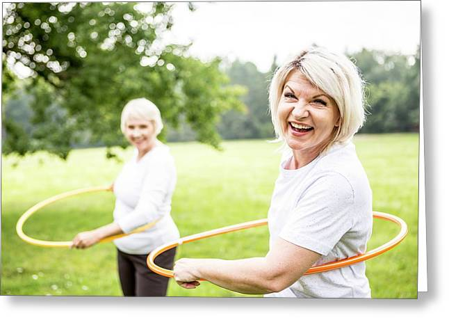 Two Women With Plastic Hoops Greeting Card by Science Photo Library