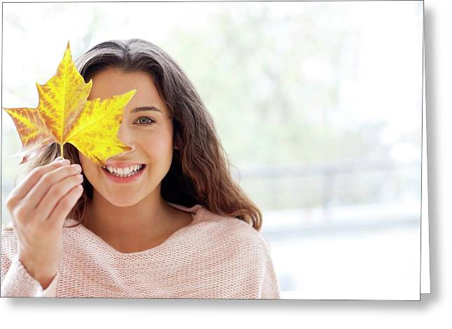 Woman Holding Leaf In Front Of Face Greeting Card by Ian Hooton