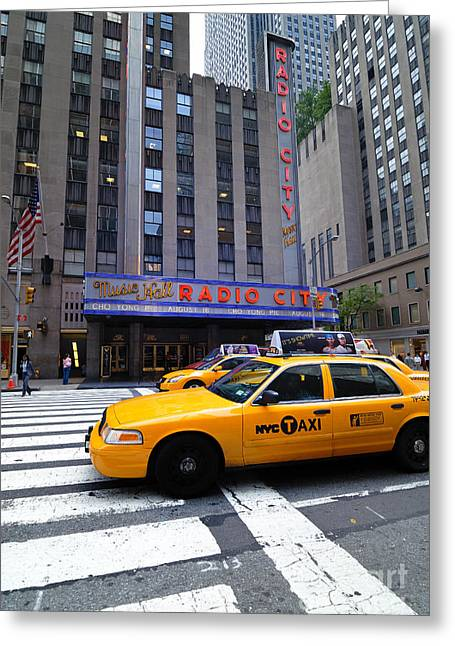 Yellow Cabs Pass In Front Of Radio City Music Hall Greeting Card by Amy Cicconi