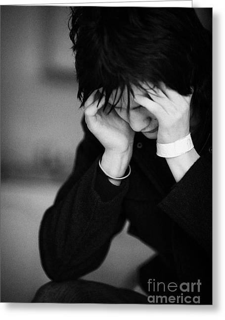 Young Dark Haired Teenage Man Sitting With His Head In His Hands Staring At The Floor Greeting Card by Joe Fox