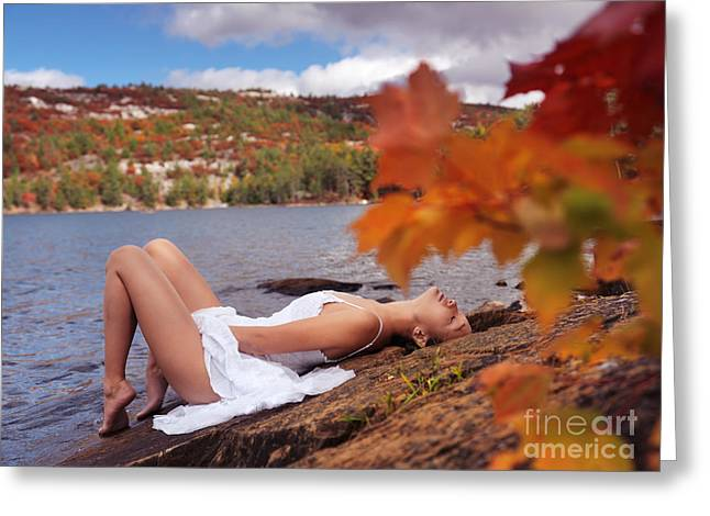 Young Woman In White Dress Lying On Shore Of Lake In Fall Greeting Card