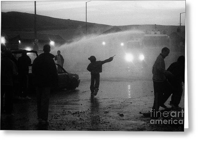 Youths Rioting Throwing Stones With Burned Out Car Being Hit By Water Canon On Crumlin Road At Ardoy Greeting Card by Joe Fox
