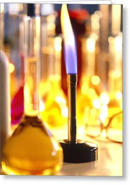 Lit Bunsen Burner With Volumetric Flasks Greeting Card by Tek Image