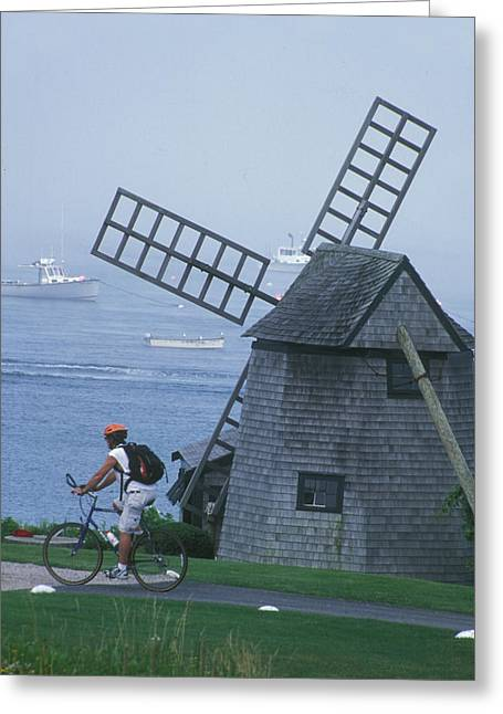 A Bicyclist Rides Past A Greeting Card