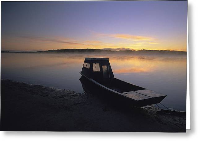 A Boat Sits On The Calm Yukon River Greeting Card by Michael Melford