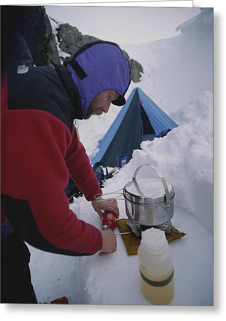 A Climber Cooks At A Snowy Camp High Greeting Card by Gordon Wiltsie