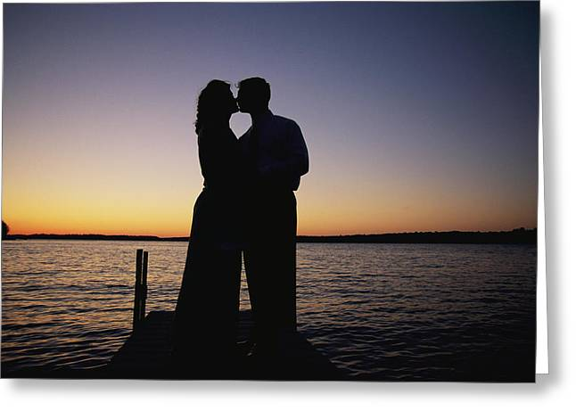 A Couple Shares A Kiss On A Lakefront Greeting Card by Joel Sartore