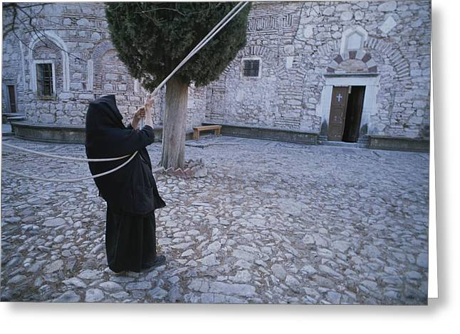 A Nun Pulls On Ropes In A Courtyard Greeting Card