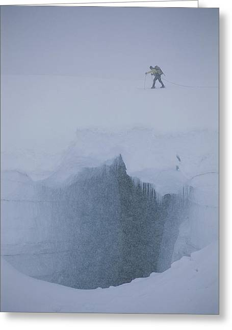 A Skier Above A Deep Glacier Crevasse Greeting Card by John Burcham
