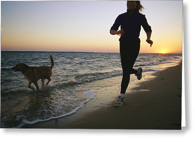 A Woman And Her Dog Run On The Beach Greeting Card by Skip Brown