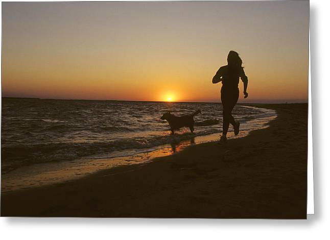 A Woman And Her Dog Running Greeting Card