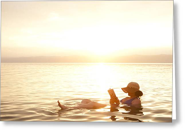 A Woman Reads A Book While Floating Greeting Card by Taylor S. Kennedy