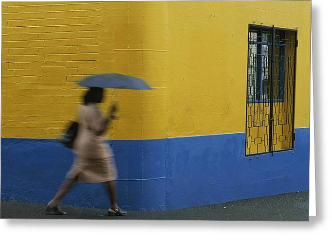 A Woman Runs Past A Yellow And Blue Greeting Card by Michael Melford