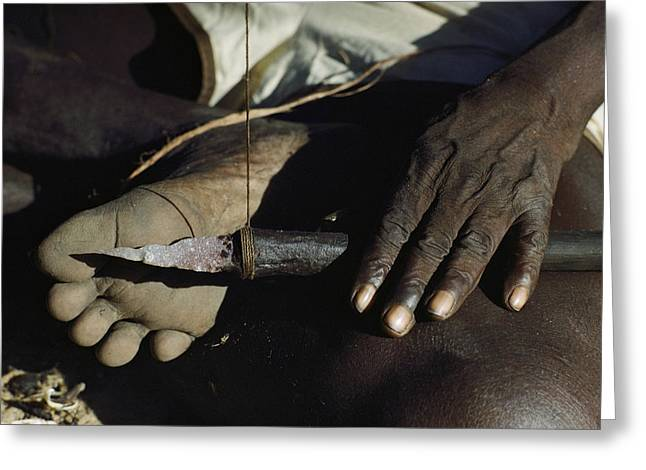 An Aborigine Hafts A Spearpoint Greeting Card by Ira Block