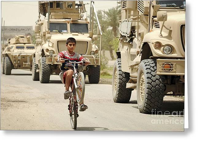 An Iraqi Boy Rides His Bike Past A U.s Greeting Card by Stocktrek Images