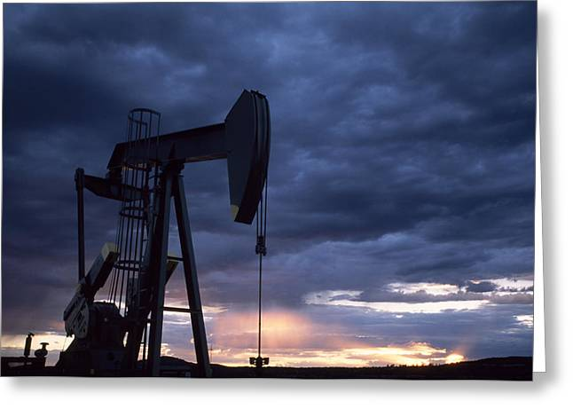 An Oil Rig Silhouetted At Sunset Greeting Card by Joel Sartore