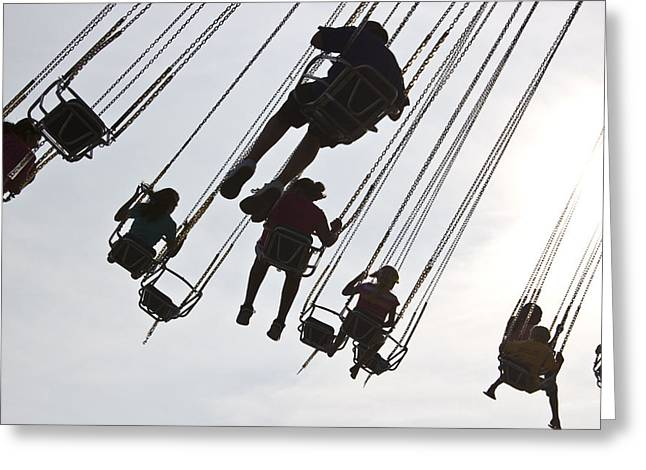 Carnival Goers Enjoy A Ride At An Greeting Card