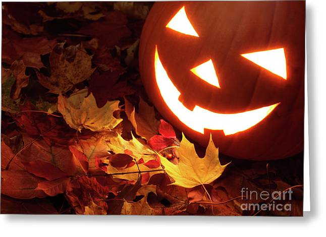 Carved Pumpkin On Fallen Leaves Greeting Card by Oleksiy Maksymenko