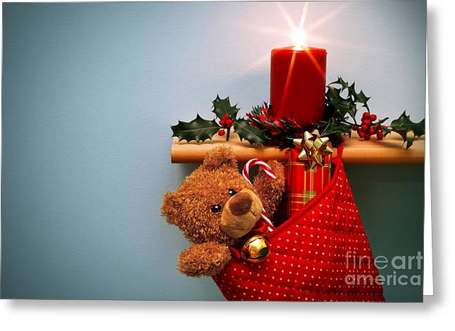 Christmas Stocking Filled With Presents With Candle And Holly. Greeting Card by Richard Thomas