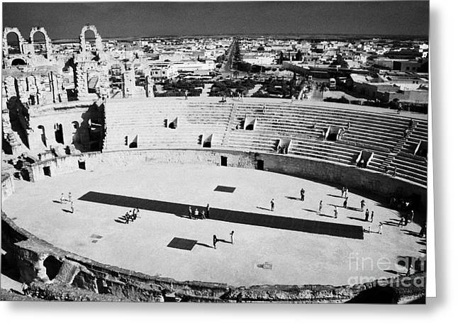 distant straight roman road leading through el Djem towards tourists the old roman colloseum arena Greeting Card