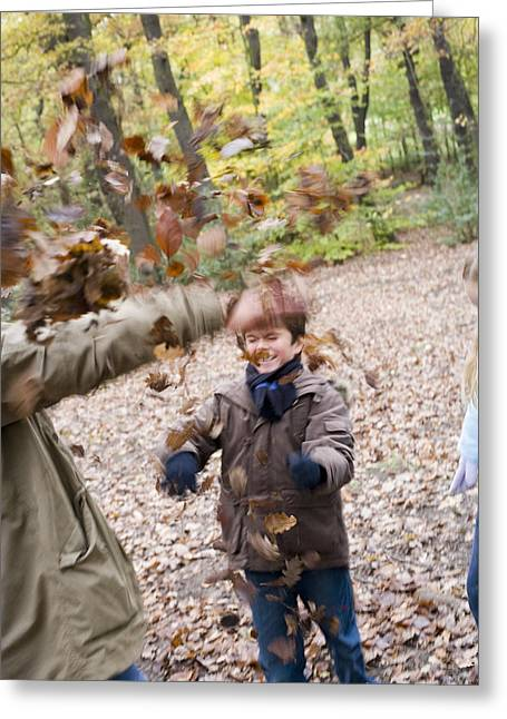 Father And Son Playing In A Wood Greeting Card by Ian Boddy