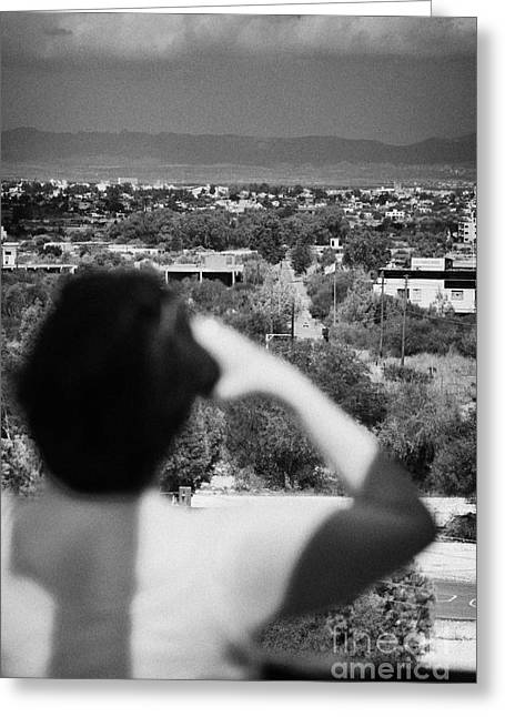 female tourist using binoculars to overlook the UN buffer zone in the green line cyprus Greeting Card by Joe Fox