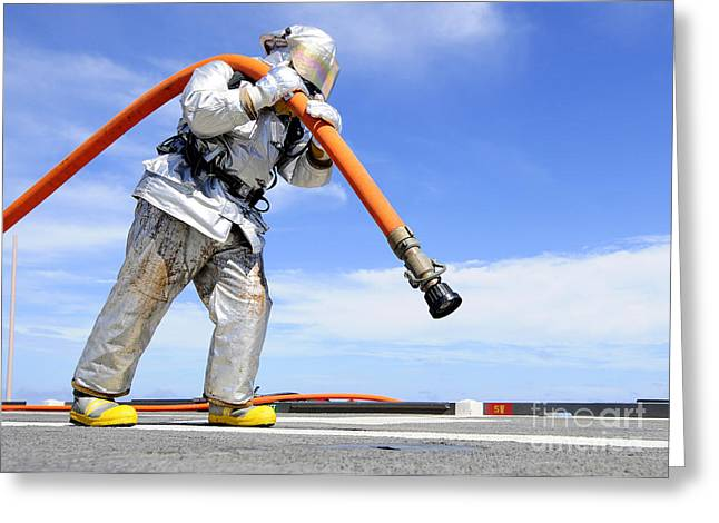 Firefighter Carries A Charged Hose Greeting Card by Stocktrek Images