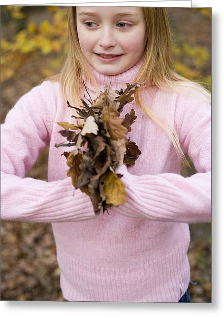 Girl Holding Autumn Leaves Greeting Card by Ian Boddy