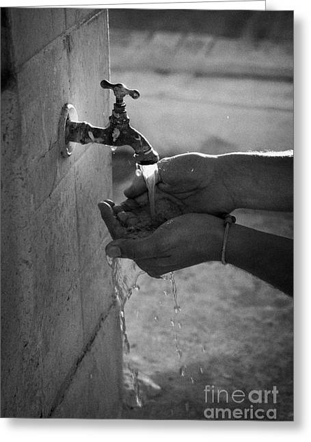 Hispanic Man Cupping Water And Washing Hands At Outdoor Tap Greeting Card by Joe Fox