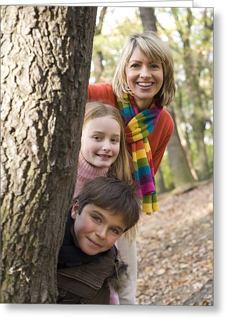 Mother And Children Playing In A Wood Greeting Card by Ian Boddy